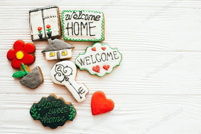 Delicious key, house, plant,window,heart and welcome sign cookies on white wood
