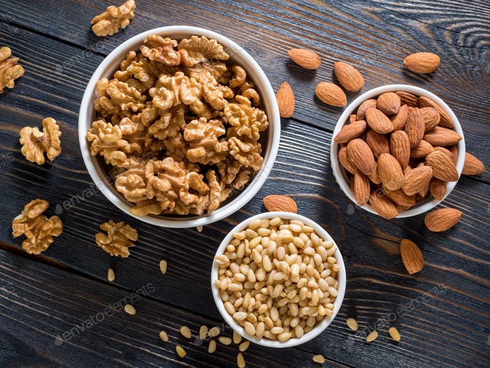 assorted nuts in white bowl on wooden dark background, mix of walnuts, almonds and cedar, top view