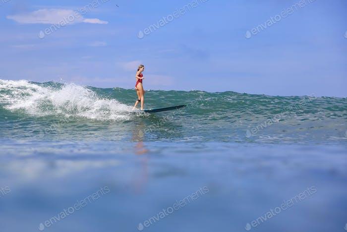 Female surfer in red bikini on a blue wave
