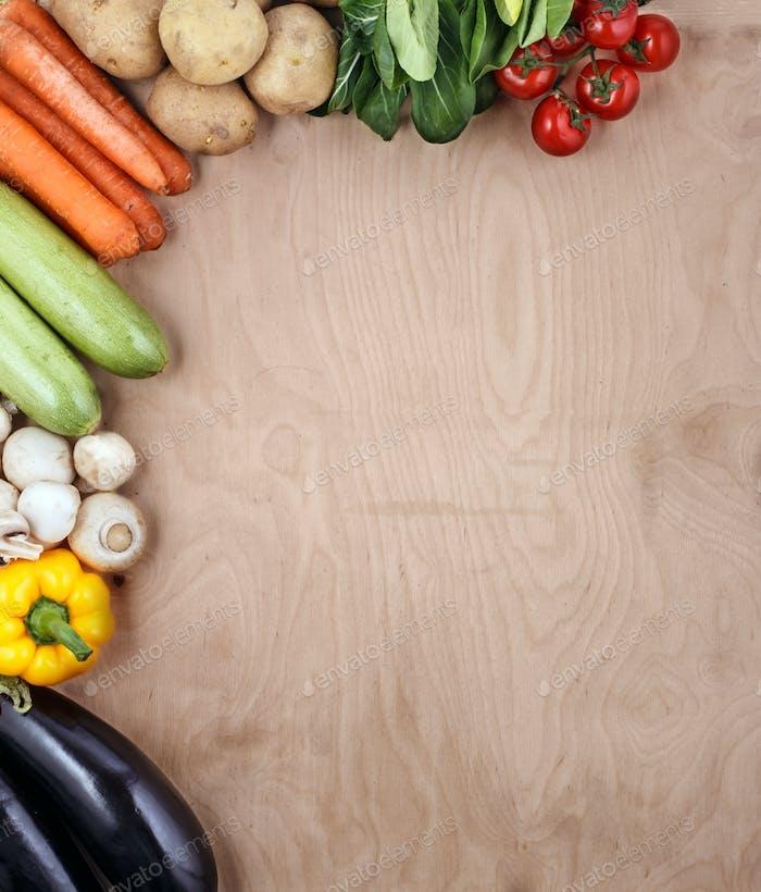 Gemüse auf Holzhintergrund mit Platz für Text.
