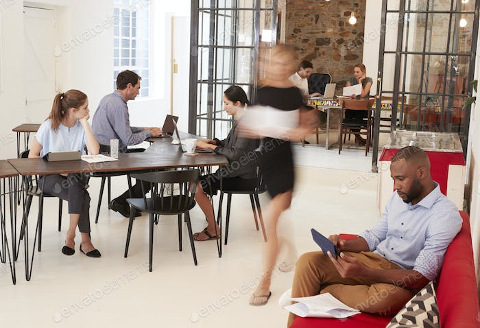 Young professionals working in a busy open plan office