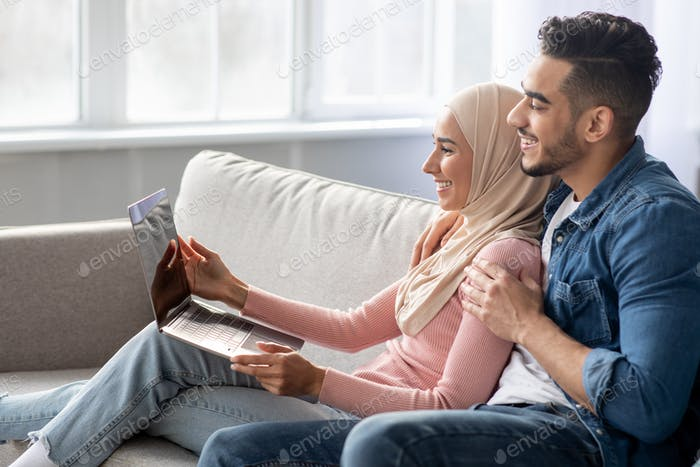 Side view of muslim couple using laptop at home