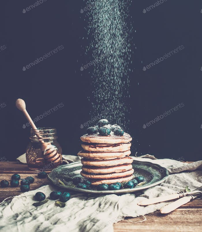 Pancake tower with fresh blueberry and mint on a rustic metal plate.