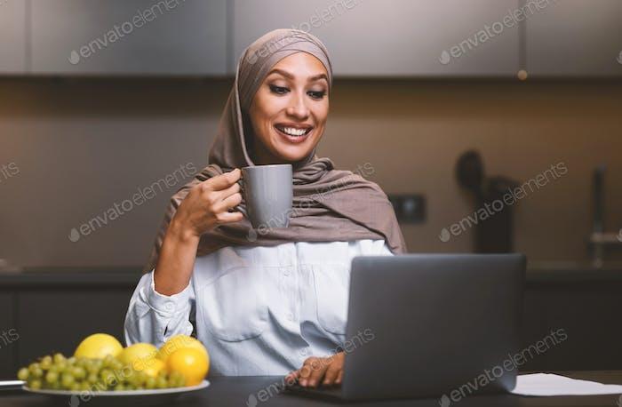 Muslim Woman At Laptop Watching Movie Drinking Coffee In Kitchen