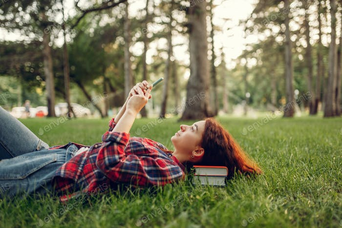 Female student with phone lying on the grass