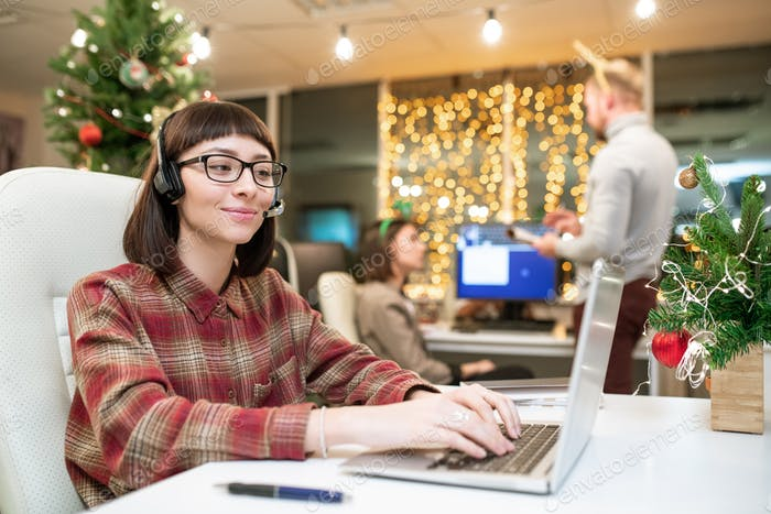Pretty young brunette operator with headset typing on laptop keypad by workplace