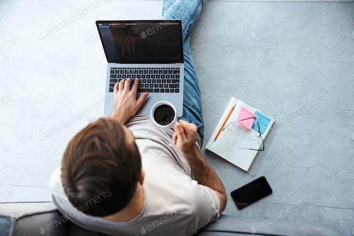 Attraktiver intelligenter junger Mann sitzt auf einem Boden im Wohnzimmer