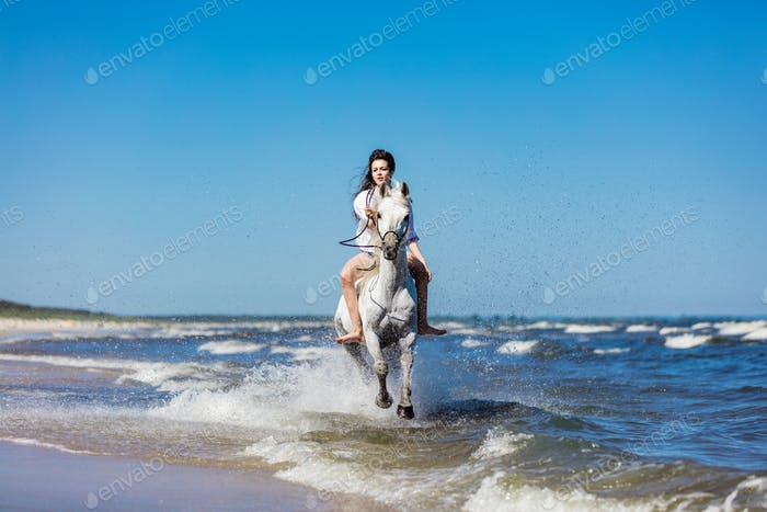 Girl galopading on a white horse in the sea