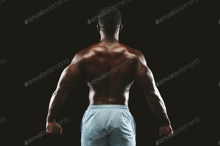Unrecognizable black sportsman showing strong back muscles