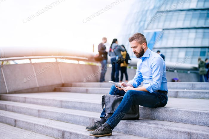 Manager mit Tablet, sitzend auf der Treppe, London, Rathaus