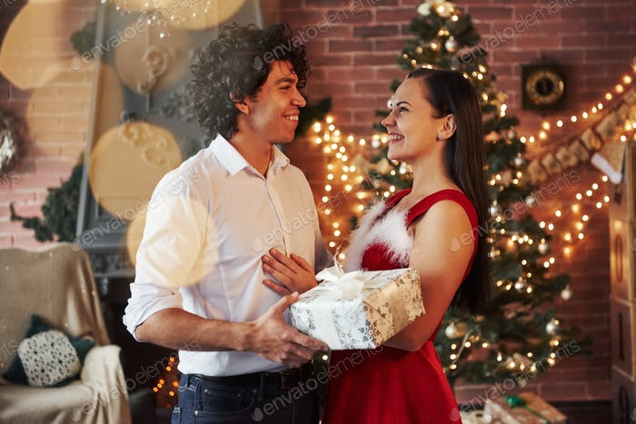 Guy with curly hair gives girl Christmas gift