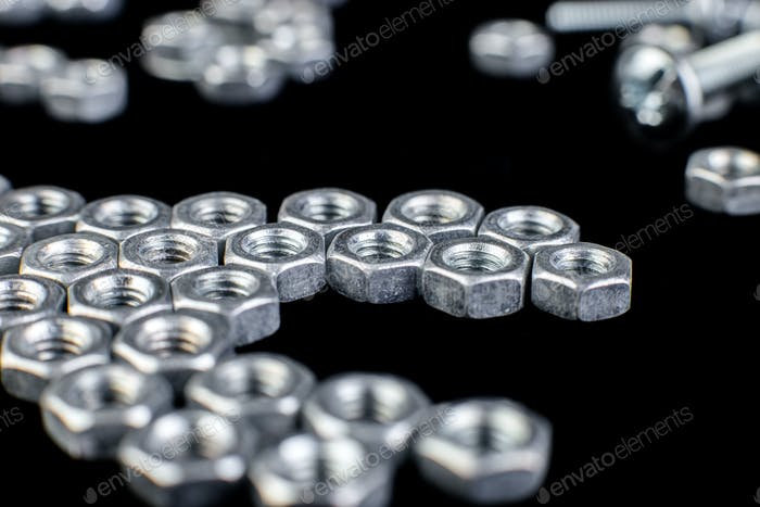 Metal nuts, bolts on black background. Flat lay. Macro.