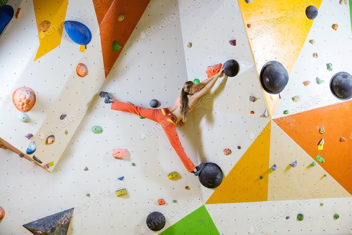 Young woman climbing challenging bouldering route