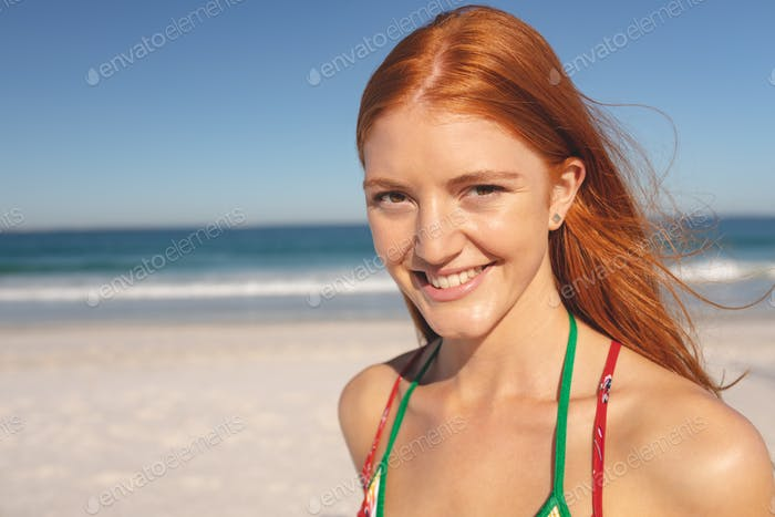 Portrait of Caucasian happy redhead woman standing on the beach