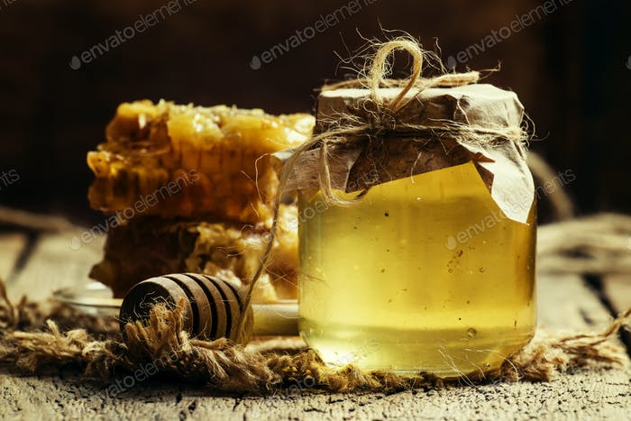 Mountain honey in a glass jar and honeycomb