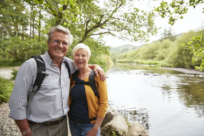 Portrait Of Senior Couple Hiking Along Path By River In UK Lake District