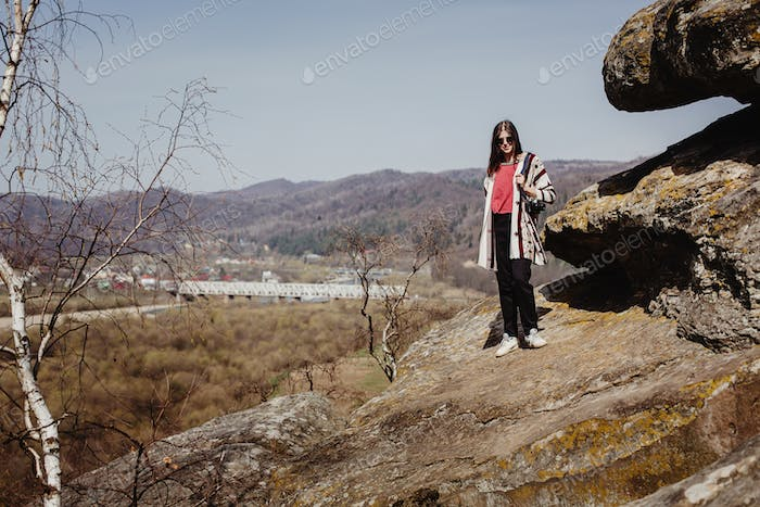 Hipster woman traveling, standing on cliff with photo camera and looking at river canyon