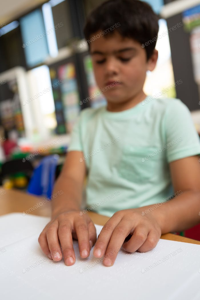 Front view of a blind Caucasian schoolboy reading a braille book at desk in the classroom at school
