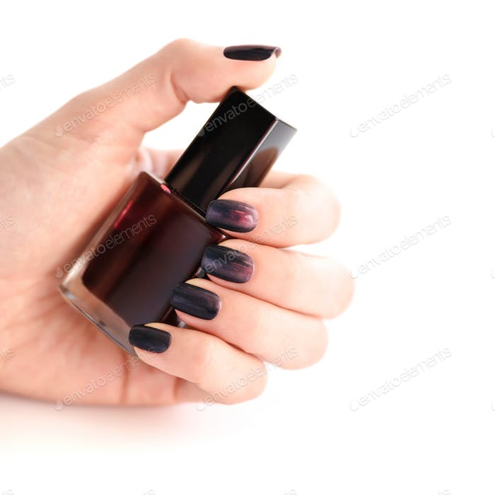 Hand of a woman with dark manicure and nail polish bottle on whi