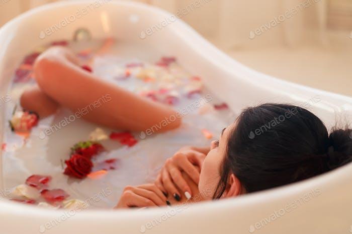 Brunette woman relaxing in the milk bath.