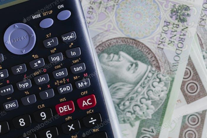 Calculadora y billetes de moneda Zloty polacos sobre una mesa