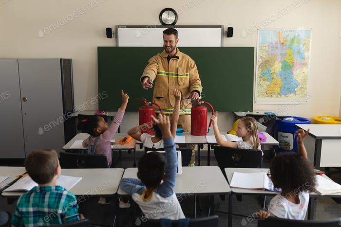 Schoolkids raising hands while firefighter teaching about fire safety of elementary school