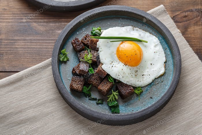 Breakfast with fried egg and croutons, close view copy space