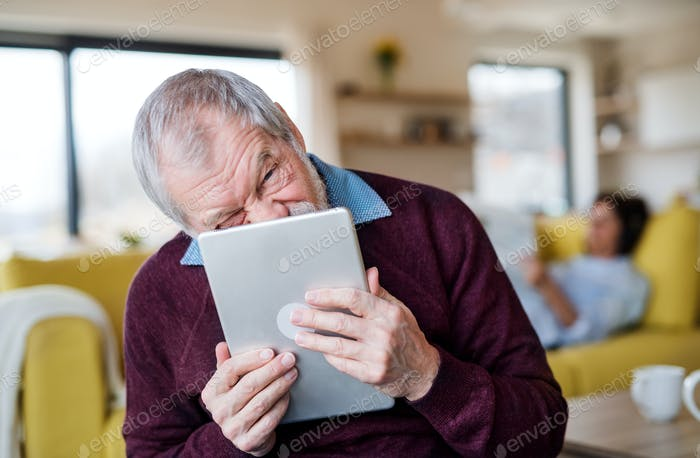 Senior man with tablet indoors at home, making funny faces
