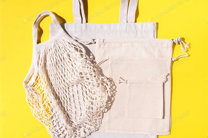 Mesh and cotton bags with on yellow background. Sustainable lifestyle. Zero waste concept. No