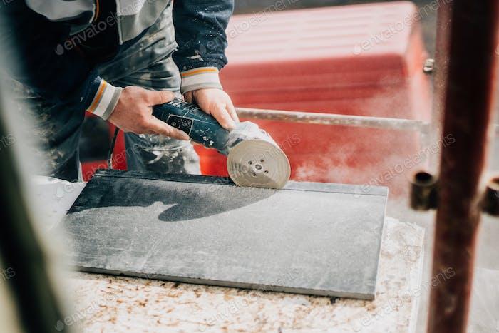 Details der Arbeiter schneiden Stein Marmor mit Winkelschleifer auf der Baustelle