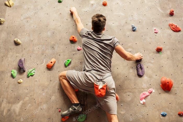 young man exercising at indoor climbing gym
