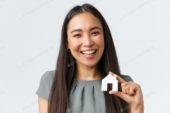 Insurance, loan, real estate and family concept. Close-up of smiling beautiful asian woman buying