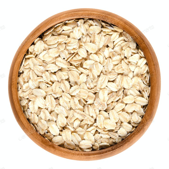 Oatmeal, rolled oats in wooden bowl over white