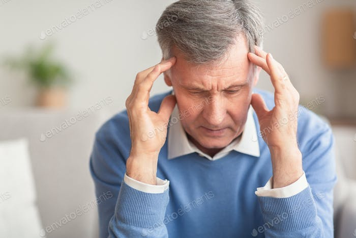 Senior Man Suffering From Migraine Sitting On Sofa At Home