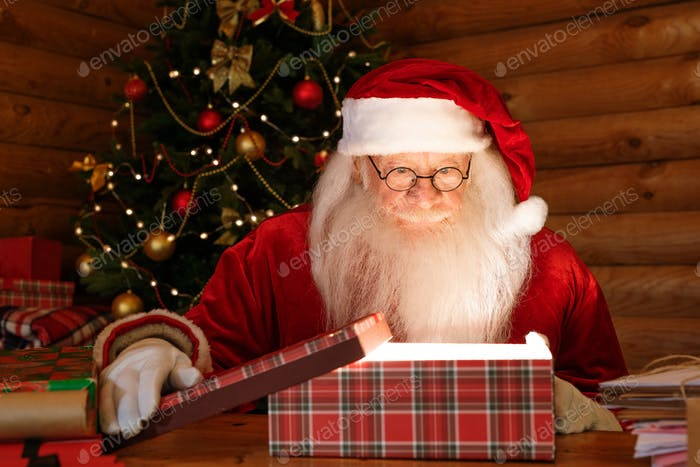Santa Claus looking at light in open giftbox with amazement
