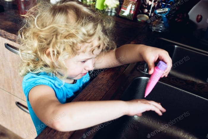 A small curly-haired blonde girl washes her toy in the sink.