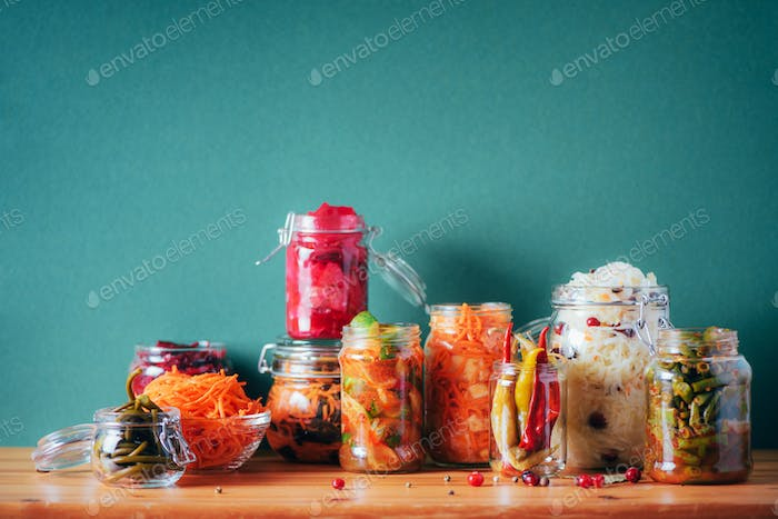 Assortment of various fermented and marinated food over wooden background, copy space. Fermented