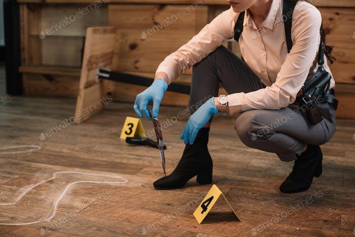 abgeschnittene Ansicht einer weiblichen Detektivin, die am Tatort Beweise sammelt