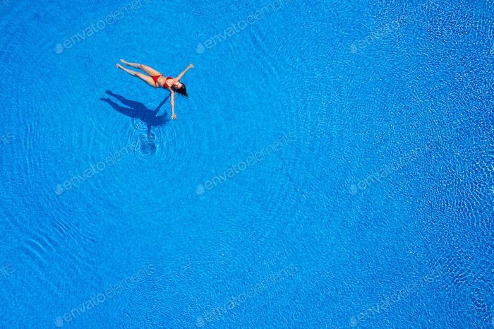 View from the top as a woman in a red swimsuit lying on her back in the pool. Relaxing concept