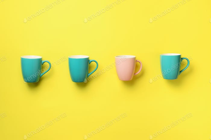 Pattern from blue and pink cups over yellow background. Birthday party celebration, baby shower