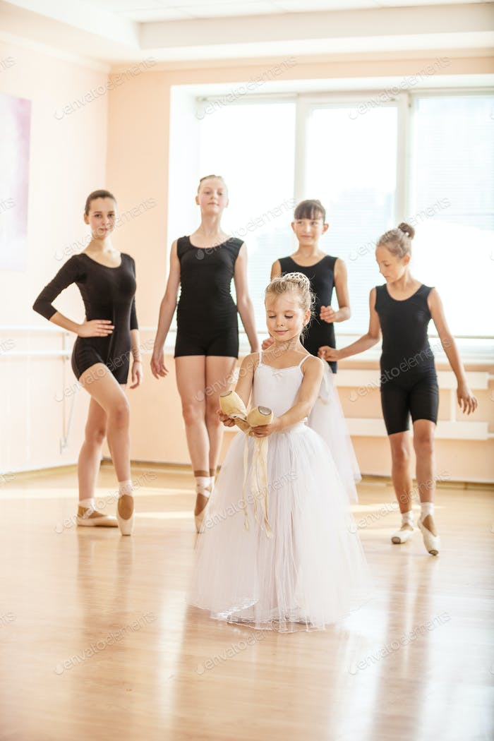 Little girl holding pointe shoes, older ballet danding students in the background