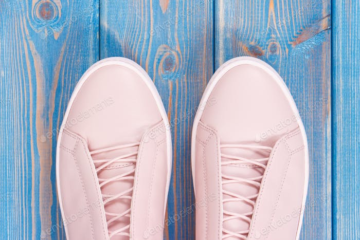 Pair of pink womanly leather shoes on old blue boards