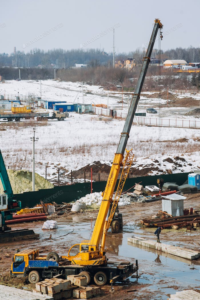 Crane beam machinery and bulldozer on building construction site on background of dirty ground
