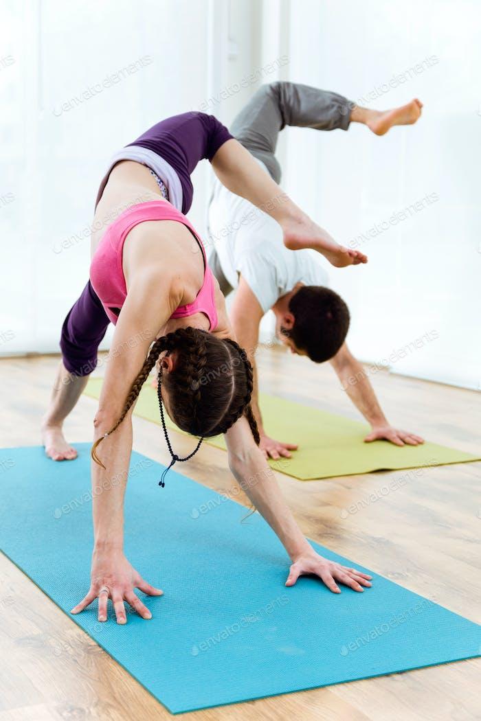 Schönes junges Paar praktiziert Yoga zu Hause.