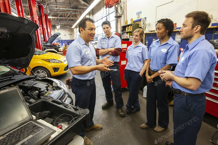 Men and women of diverse ethnic backgrounds, a team of mechanics in an auto repair shop