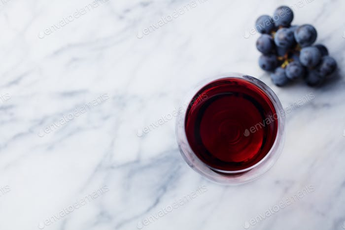 Red Wine in Glass with Fresh Grape on Marble Table Background. Top view. Copy space.