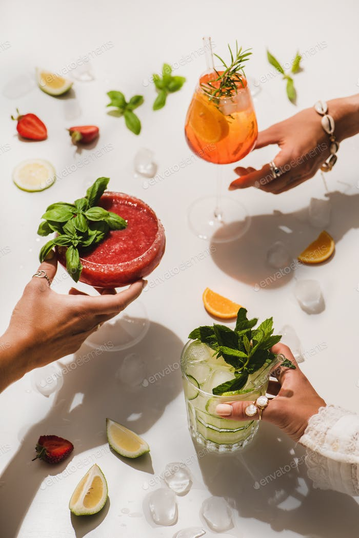 Poplular Sommer Alkohol Cocktails bei Frauen Hände über weißen Hintergrund