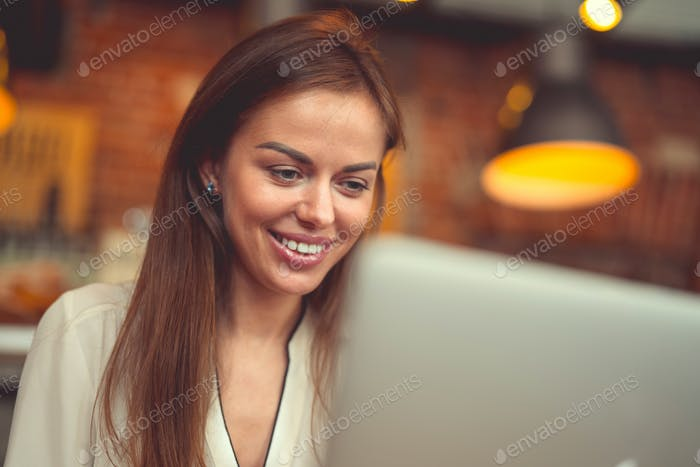 Smiling woman with a laptop at work