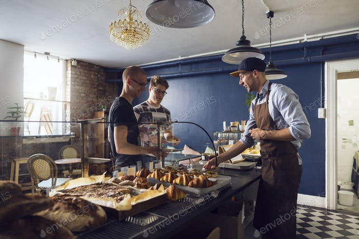 Customers and worker in bakery