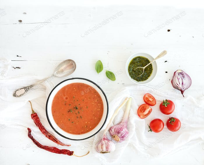 Gazpacho soup in rustic metal bowl with fresh tomatoes, green sauce, chili, garlic and basil